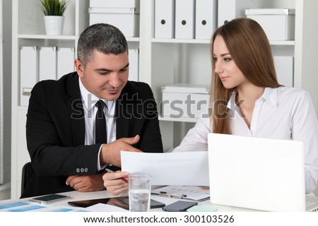 Young beautiful business woman consulting with her colleague. Partners discussing documents and ideas - stock photo