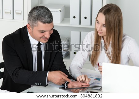 Young beautiful business woman consulting with her male colleague showing something on tablet PC. Partners discussing documents and ideas - stock photo