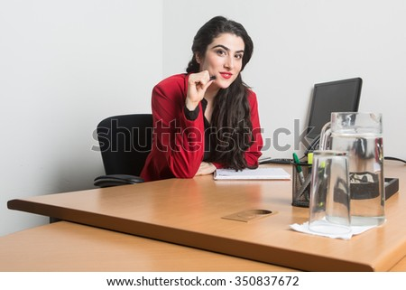 Young beautiful business woman in the office, wearing a red jacket, looking bored