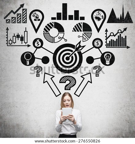 Young beautiful business woman is thinking about business optimisation process by working on the tablet. Drawn business flowchart on the concrete wall. - stock photo