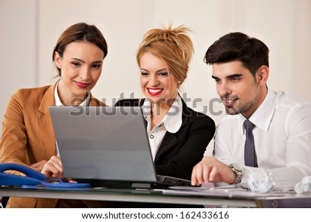 Young beautiful business woman smiling with a laptop in front of her and two colleagues business people in the back - stock photo