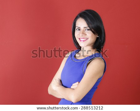 Young beautiful business woman smiling with her arms crossed and looking confident - stock photo