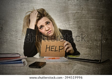 young beautiful business woman suffering stress working at office computer desk asking for help feeling tired and desperate looking overworked pulling her hair overwhelmed and frustrated grunge style - stock photo