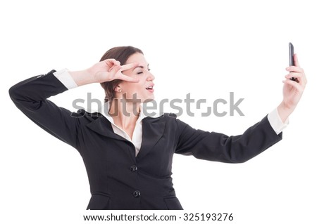 Young, beautiful business woman taking a selfie with smartphone showing peace or victory gesture
