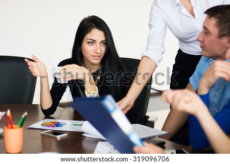 Young beautiful business woman with a cup of coffee to colleagues explaining the idea. Business discussion - stock photo
