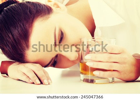 Young beautiful business woman with glass of whisky or rum.