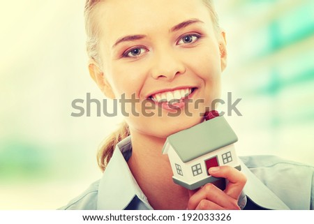 Young beautiful business woman with house model - real estate - stock photo