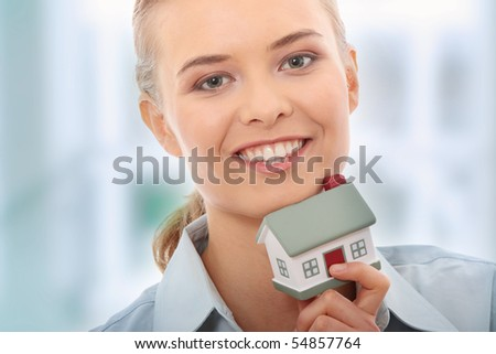 Young beautiful business woman with house model - real estate