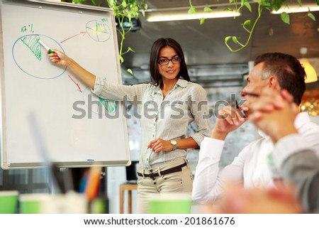 Young beautiful businesswoman explaining graph to his colleagues - stock photo
