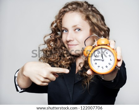 Young beautiful businesswoman holding a clock - stock photo