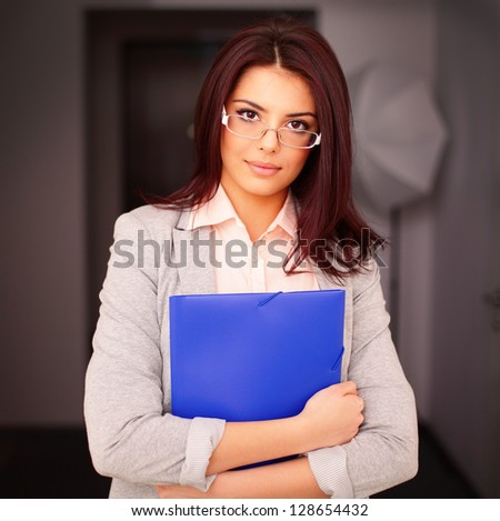 Young beautiful businesswoman in office holding a folder