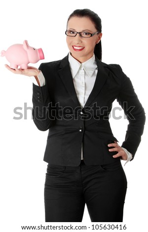 Young beautiful businesswoman is showing pink piggybank. She's standing and wearing black suit and glasses. Isolated on the white background. - stock photo