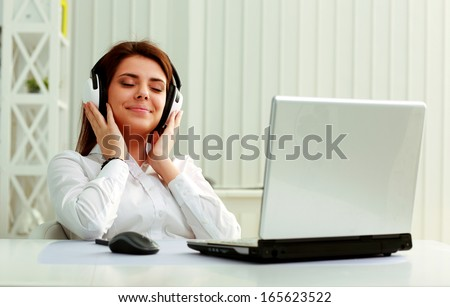 Young beautiful businesswoman listening music in headphones at office - stock photo
