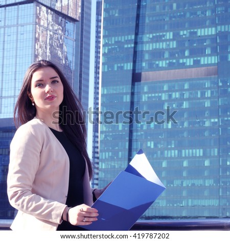 Young beautiful businesswoman outdoors at skyscraper background