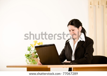 young beautiful businesswoman sitting with laptop in office - stock photo