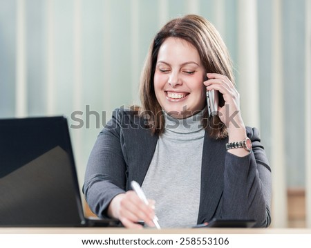 Young beautiful businesswoman talking on the mobile phone in office. - stock photo