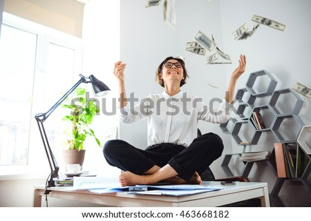 Young beautiful businesswoman throwing up money, sitting on table.