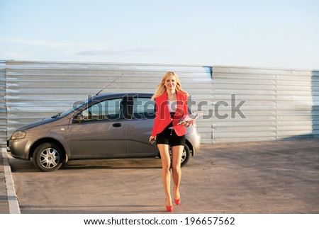 Young beautiful businesswoman with her car - stock photo