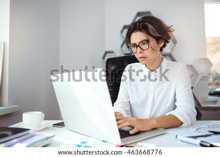 Young beautiful businesswoman working with laptop at workplace in office.