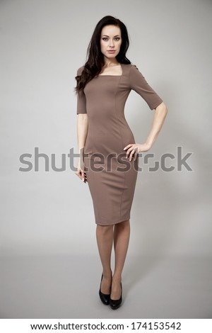 Young beautiful caucasian brunette in fashion dress posing on grey background  - stock photo