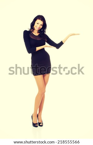 Young beautiful caucasian brunette in gorgeous sexy dress showing copy space on her palm. - stock photo