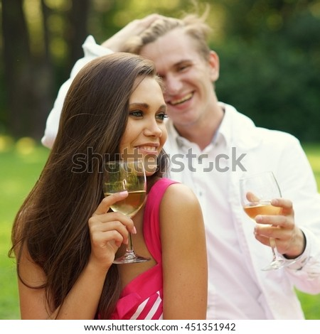 Young beautiful caucasian couple hugging and drinking wine at picnic in summer park on green grass