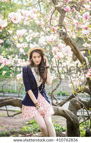 Young beautiful caucasian girl in a blossoming spring magnolia garden. The girl in the garden morning. Boho style. Portrait, vertical. The girl in the hat, necklace and earrings. - stock photo