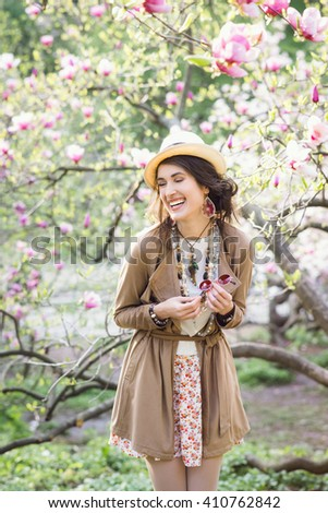 Young beautiful caucasian laughing girl in a blossoming spring magnolia garden. The girl in the garden morning. Boho style. Portrait, vertical. The girl in the hat, necklace and earrings. - stock photo