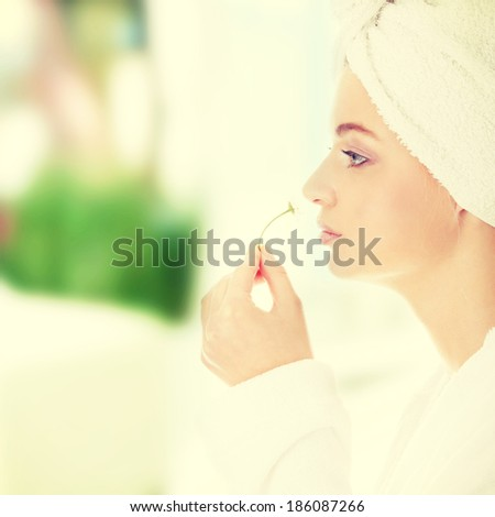 Young beautiful caucasian woman after bath with flower - stock photo