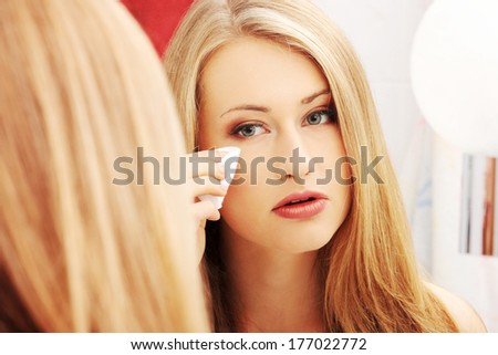 Young beautiful caucasian woman cleaning her face with cotton pad in the bathroom  - stock photo