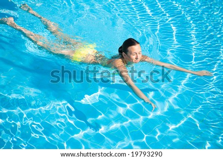 Young beautiful caucasian woman in bikini swimming in pool