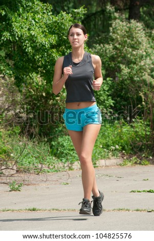 Young beautiful caucasian woman jogging in summer park - stock photo