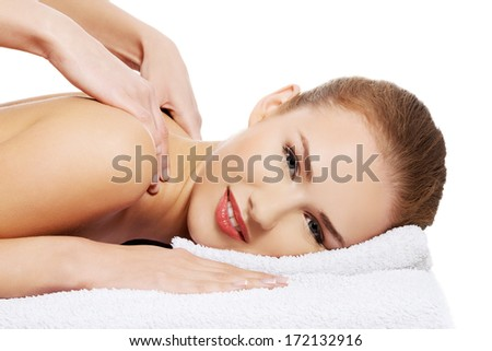 Young beautiful caucasian woman lying on a massage table and is being massaged. Isolated on white. - stock photo