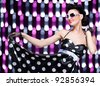 young beautiful caucasian woman posing, retro styling, over abstract lights - stock photo