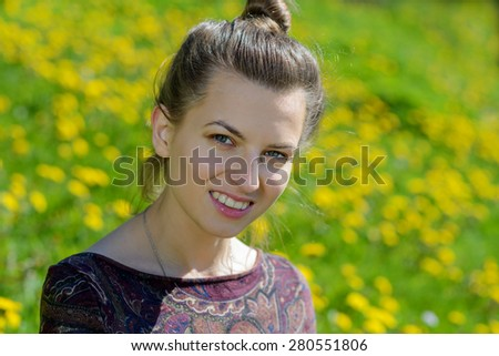Young beautiful caucasian woman sitting on a sunlit meadow. - stock photo