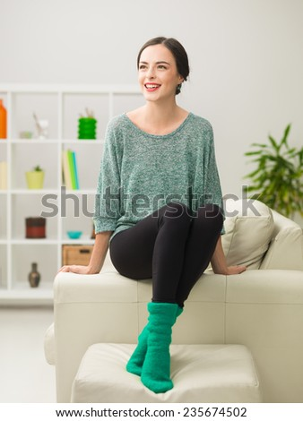 young beautiful caucasian woman sitting on couch at home, having fun and laughing - stock photo