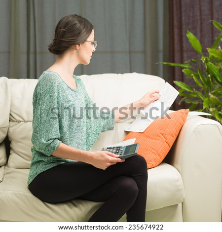 young beautiful caucasian woman sitting on sofa at home, doing her accounts - stock photo