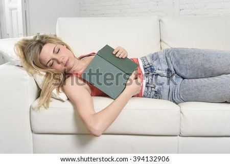 young beautiful caucasian woman sleeping while reading book or studying lying comfortable on home couch or sofa looking happy and relaxed in culture concept and lifestyle - stock photo