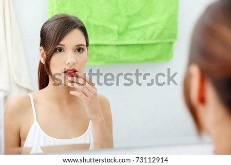 Young beautiful caucasian woman stands about a mirror in a bathroom