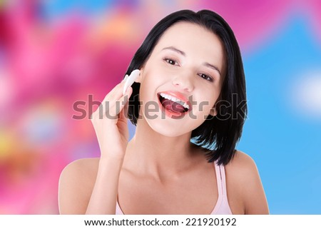 Young beautiful caucasian woman using a cotton pad to remove her make-up.