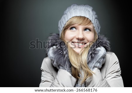 Young beautiful Caucasian woman with blue eyes in winter coat and hat dreamily looking away. - stock photo