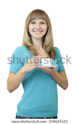 Young beautiful Caucasian woman with blue eyes waist up studio shot on white background (isolated). Looking at camera and smiling. Holding a white coffee cup on a saucer. - stock photo