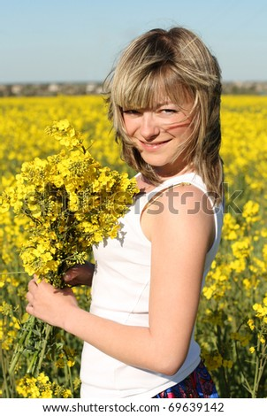 young beautiful cheerful woman on blooming field in summer - stock photo