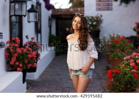 Young beautiful cheerful woman walking on old street at tropical town. Pretty girl looking at you and smiling - stock photo