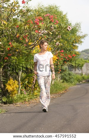 Young beautiful cheerful woman walking on the street full of flower - stock photo