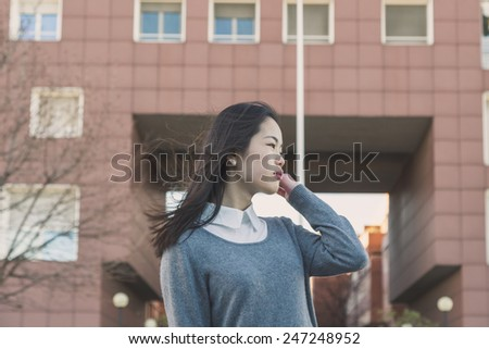 Young beautiful Chinese girl with long hair posing in the city streets