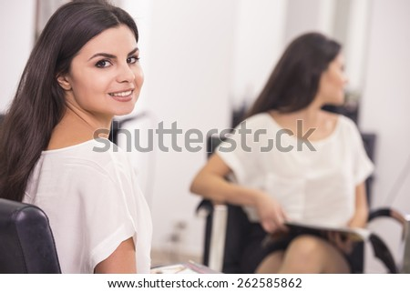 Young beautiful client with long straight brunette hair sitting in the chair in hairdressing salon. - stock photo