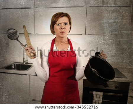 young beautiful cook woman confused and frustrated face expression wearing red apron holding rolling pin and cooking pot at home kitchen in domestic stress and lifestyle concept grunge dirty edit - stock photo