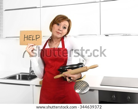 young beautiful cook woman in angry upset and frustrated face expression wearing red apron asking for help holding rolling pin and pot at home kitchen in domestic stress and lifestyle concept - stock photo