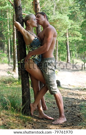 Young beautiful couple are kissing at the beach - stock photo